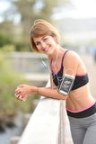 Young woman in running outfit with smartphone on her arm Stock Photos