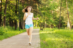 Young woman running in park Royalty Free Stock Photos