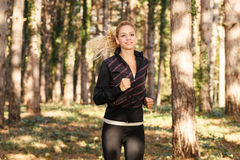 Young woman running through the park Royalty Free Stock Photo