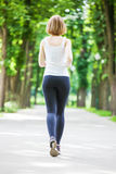 Young woman running in the park. Royalty Free Stock Photography