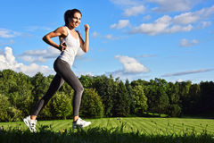 Young woman running in the park during sport training Stock Photo