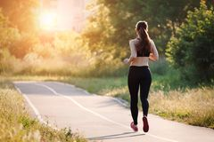 Young woman running in park stock image