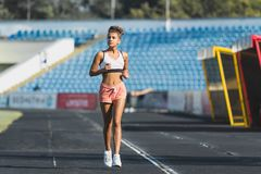 Young woman running on racetrack during training session stock photos