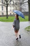 Young woman running through the rain Royalty Free Stock Photo