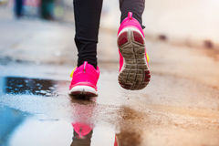 Young woman running in rainy weather Stock Image