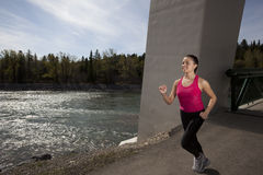 Young Woman Running Beside River Royalty Free Stock Images