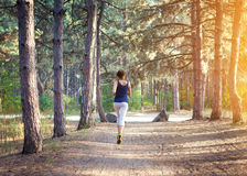 Young woman running on a rural road in forest Royalty Free Stock Photos