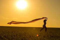 Young woman running on a rural road at sunset in Stock Photography