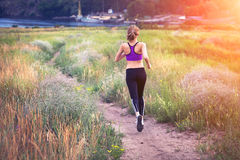 Young woman running on a rural road at sunset Stock Photography