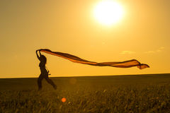 Young woman running on a rural road at sunset in summer field. Lifestyle sports freedom background Stock Photography