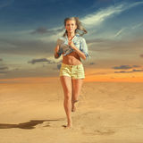 Young woman running on the sand Stock Photos