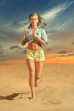 Young woman running on the sand Royalty Free Stock Image