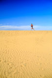 Young woman running on sand desert dunes Stock Images