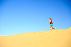 Young woman running on sand desert dunes Royalty Free Stock Photography