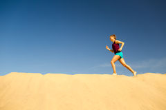 Young woman running on sand desert dunes Royalty Free Stock Photos