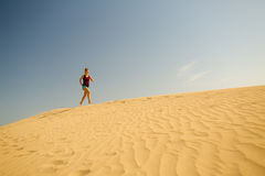 Young woman running on sand desert dunes Royalty Free Stock Photo