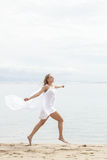Young woman running with with scarf and feeling free. Portrait of young woman running with with scarf and feeling free on the beach Stock Photography