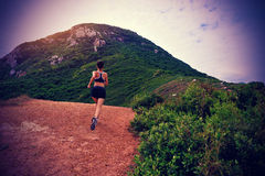 Young woman running on seaside mountain trail Stock Photos