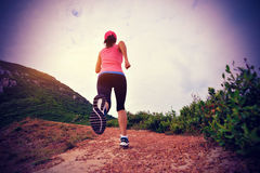 Young woman running on seaside mountain trail Royalty Free Stock Photography