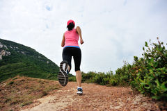 Young woman running on seaside mountain trail Royalty Free Stock Image