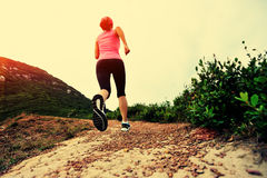 Young woman running on seaside mountain trail Royalty Free Stock Images