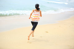 Young woman running seaside Stock Photo
