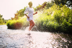 Young woman running in shallow water Stock Photography