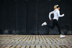 Young woman running on sidewalk in morning Stock Photos