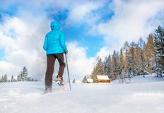 Young woman running with snow shoes in winter Royalty Free Stock Photo