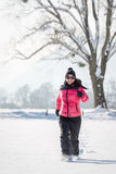 Young woman running in the snow Royalty Free Stock Photo