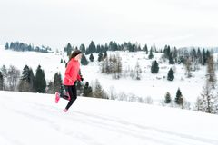 Young woman running on snow in winter mountains wearing warm clothing gloves in snowy weather royalty free stock images