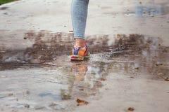 Young woman running, splashing puddles. Stock Photos