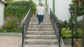 Young woman running on stairs. stock footage