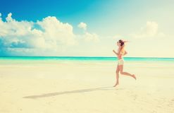 Young woman running on summer beach on coast of the ocean Stock Photos