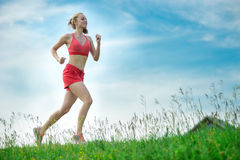 Young woman running summer park rural road. Young lady running. Woman runner running through the summer park rural road. Workout in a park. Beautiful fit girl Royalty Free Stock Image