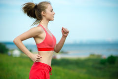 Young woman running summer park rural road. Outdoor exercises. J. Young lady running. Woman runner running through the summer park rural road. Workout in a park Royalty Free Stock Image