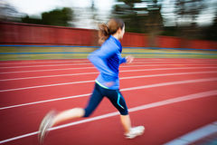 Young woman running at a track Stock Images