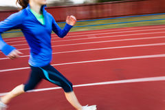 Young woman running at a track Stock Photography