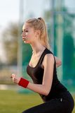 Young woman running at a track. And field stadium Royalty Free Stock Image