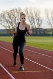 Young woman running at a track. And field stadium Stock Photography