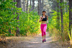 Young Woman Running on the Trail in the Beautiful Wild Forest. Active Lifestyle Concept. Space for Text. Royalty Free Stock Photo