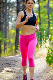 Young Woman Running on the Trail in the Beautiful Wild Forest. Active Lifestyle Concept. Space for Text. Royalty Free Stock Image