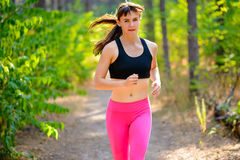 Young Woman Running on the Trail in the Beautiful Wild Forest. Active Lifestyle Concept. Space for Text. Stock Images