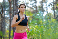 Young Woman Running on the Trail in the Beautiful Wild Forest. Active Lifestyle Concept. Space for Text. Royalty Free Stock Photos
