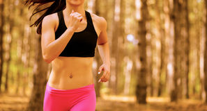 Young Woman Running on the Trail in the Beautiful Wild Pine Forest. Active Lifestyle Concept. Space for Text. Royalty Free Stock Photo