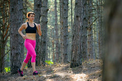 Young Woman Running on the Trail in the Beautiful Wild Pine Forest. Active Lifestyle Concept. Space for Text. Royalty Free Stock Images