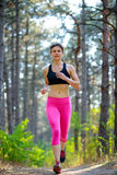 Young Woman Running on the Trail in the Beautiful Wild Pine Forest. Active Lifestyle Concept. Space for Text. Royalty Free Stock Photos