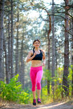 Young Woman Running on the Trail in the Beautiful Wild Pine Forest. Active Lifestyle Concept. Space for Text. Stock Photo