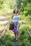 Young woman running after the train. Woman in a dress with a suitcase in his hand raised her hand and running on railroad tracks Stock Photos