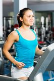 Young woman running on a treadmill Royalty Free Stock Photos